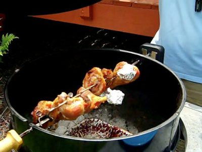 Turkey legs on a rotisserie spit in a kettle grill