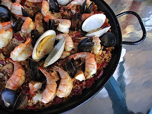 Pan full of cooked paella, covered with clams, mussels, and shrimp, on a glass table