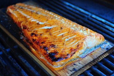 A cooked filet of salmon on a cedar plank on a grill