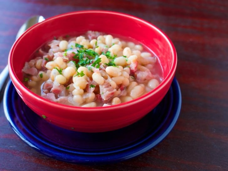 A red bowl of US Senate Bean Soup on a blue plate