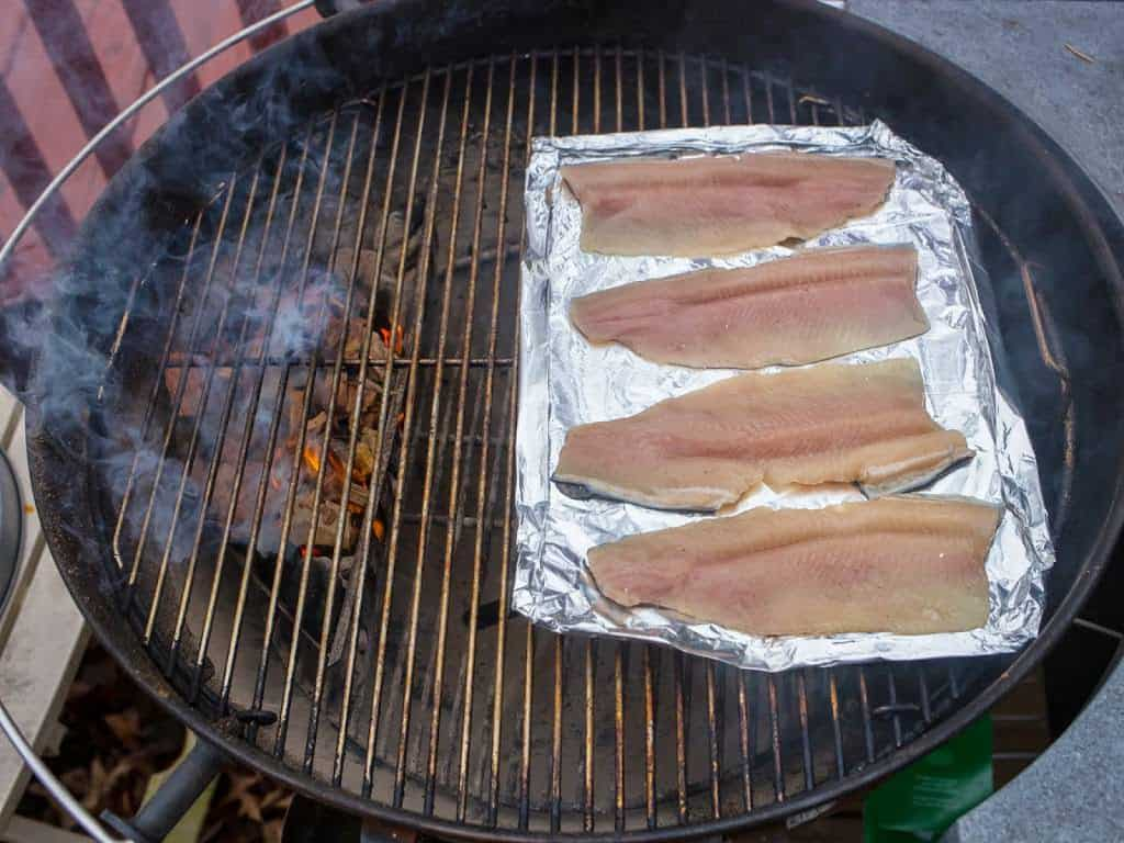 Grill Smoked Trout: trout on a foil sheet, on a grill, with smoking coals on the other side of the grill