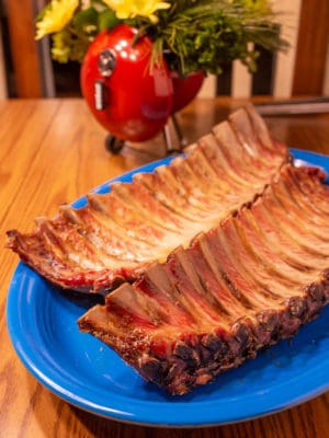 Two cooked slabs of ribs on a platter in front of a flower arrangement that looks like a kettle grill