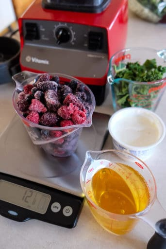 Apple juice, frozen berries on a scale, yogurt, kale and a red Vitamix blender