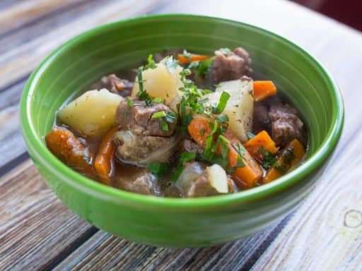 Side view of a green bowl full of stew, with chunks of potatoes, carrots, and lamb, sprinkled with parsley.
