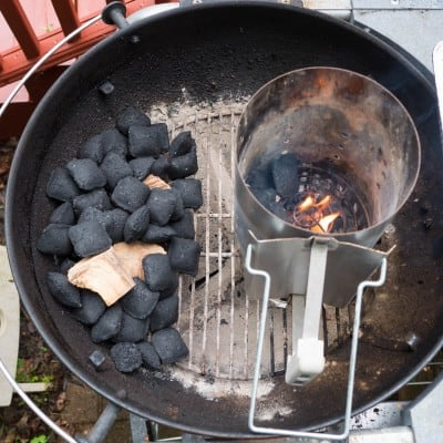Kettle grill with coals on one side and charcoal chimney on the other.