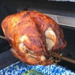 Rotisserie turkey breast on a spit in a grill above a blue speckled drip pan