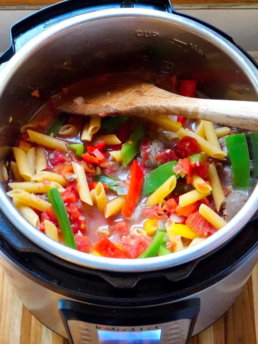 Instant Pot full of peppers, tomatoes, penne pasta and sausage with a spoon sticking out | DadCooksDinner.com