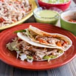 Quick Chicken Tacos on a plate with a platter of chicken and other toppings in the background
