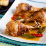 Chicken drumsticks with peppers and paprika on a white platter