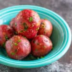 A bowl of cooked baby red potatoes sprinkled with parsley