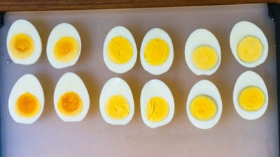 Hard-boiled egg halves on a cutting board, 4 undercooked, 4 cooked just right, 4 overcooked