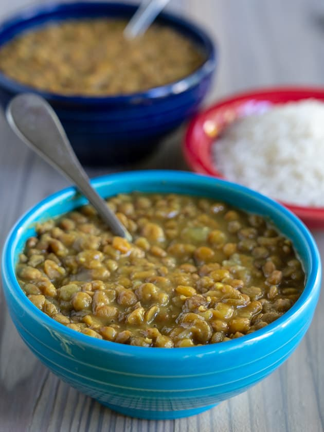 A blue bowl of lentils with a spoon in the foreground, with a bowl of rice and another bowl of lentils in the background