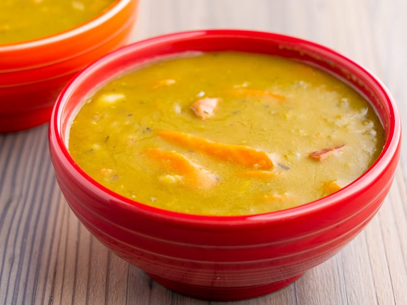 Red bowl full of green split pea soup on a wooden table
