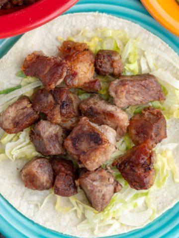 A pile of pork carnitas on shredded lettuce, piled on a tortilla, on an aqua plate