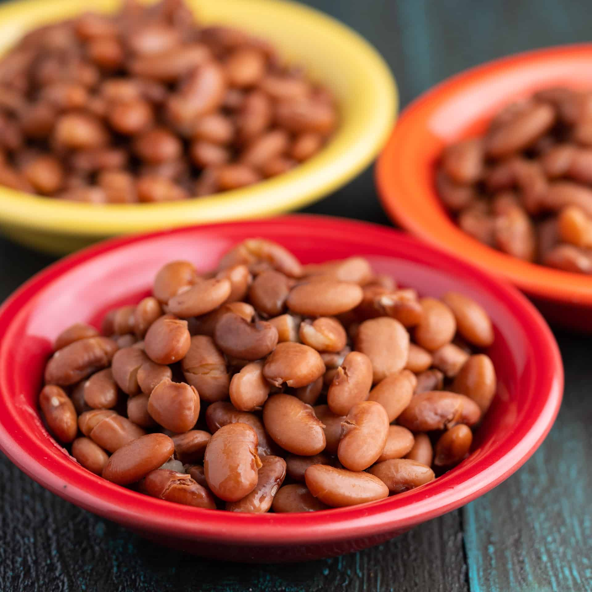 Three bowls of cooked Pinto Beans on a tabletop