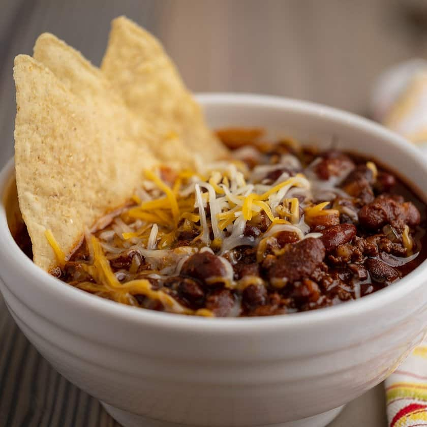 A bowl of ground beef and bean chili, with tortilla chips and cheese sprinkled on top