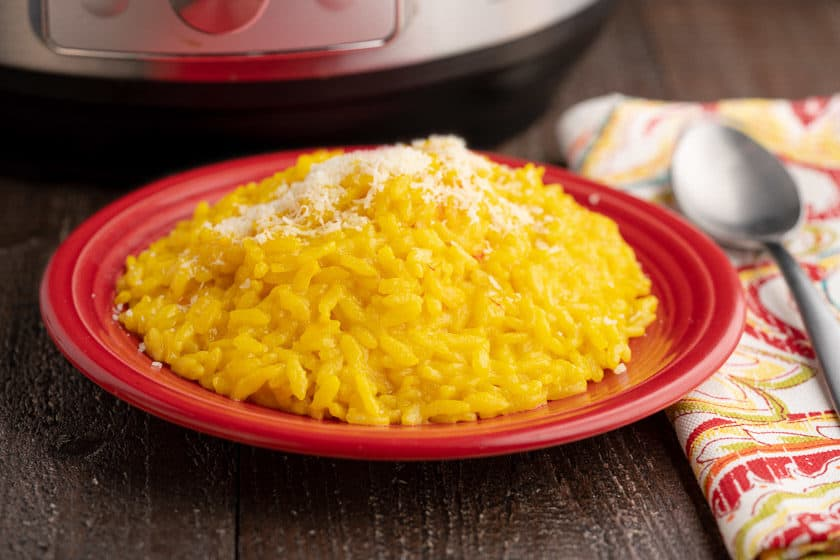 A red plate of bright yellow risotto Milanese sprinkled with grated cheese, with a napkin, spoon, and instant pot in the background