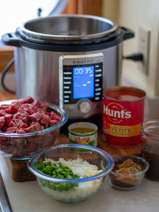 Bowl of cubed beef; bowl of onions, garlic and jalapenos; bowl of spices; cans of diced chiles and diced tomatoes, and a jar of beef broth in front of an Instant Pot pressure cooker
