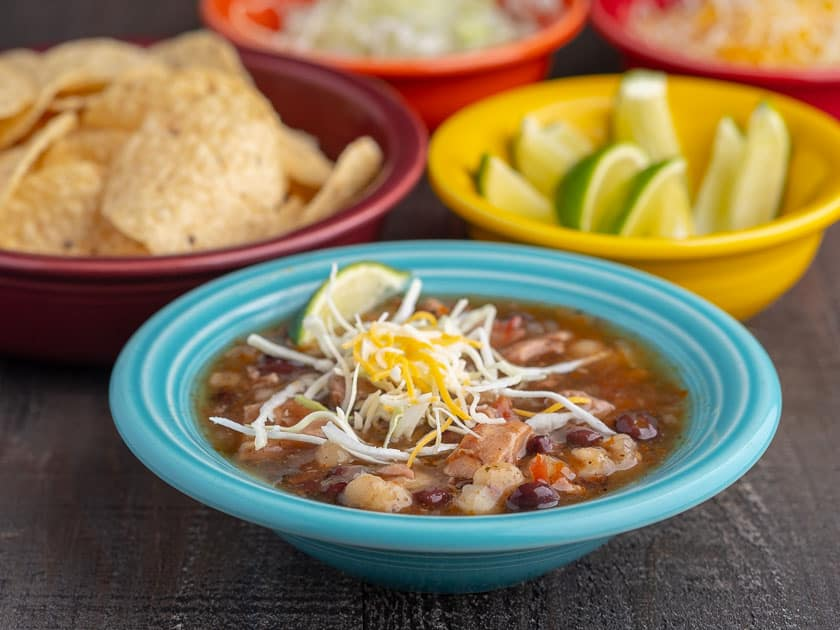 An aqua colored bowl full southwestern turkey soup, topped with shredded cabbage and cheese, with bowls of tortillas, limes, and shredded cabbage in the background, with the text Instant Pot Day-After-Thanksgiving Turkey Carcass Soup | DadCooksDinner underneath