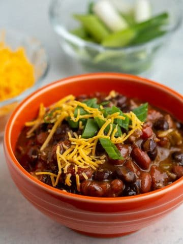 An orange bowl of turkey and bean chili, sprinkled with cheese and green onions, with a bowl of cheese and green onions in the background