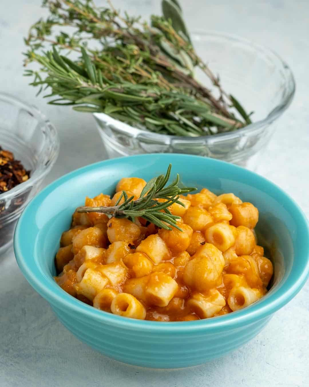 A teal bowl of pasta and chickpeas, with a sprig of rosemary on top, and a bowl of rosemary sprigs and red pepper flakes in the background.