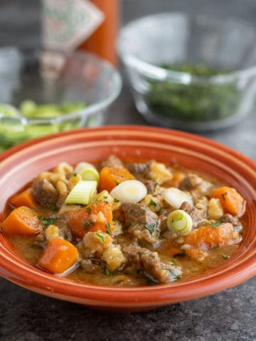 A bowl of beef brisket soup with carrots, green onions, and thyme, in an orange bowl on a slate-gray background