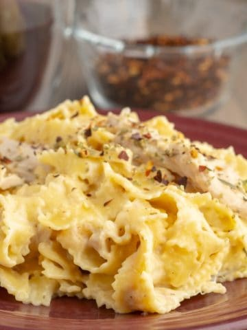 A plate of fettuccine alfredo, sprinkled with red pepper flakes
