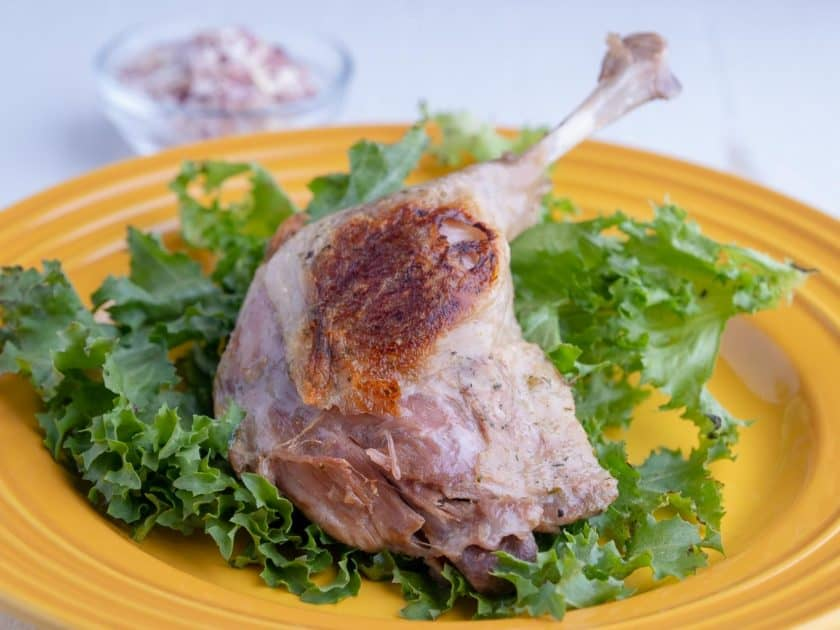 Cooked duck leg on a bed of lettuce, on a yellow plate
