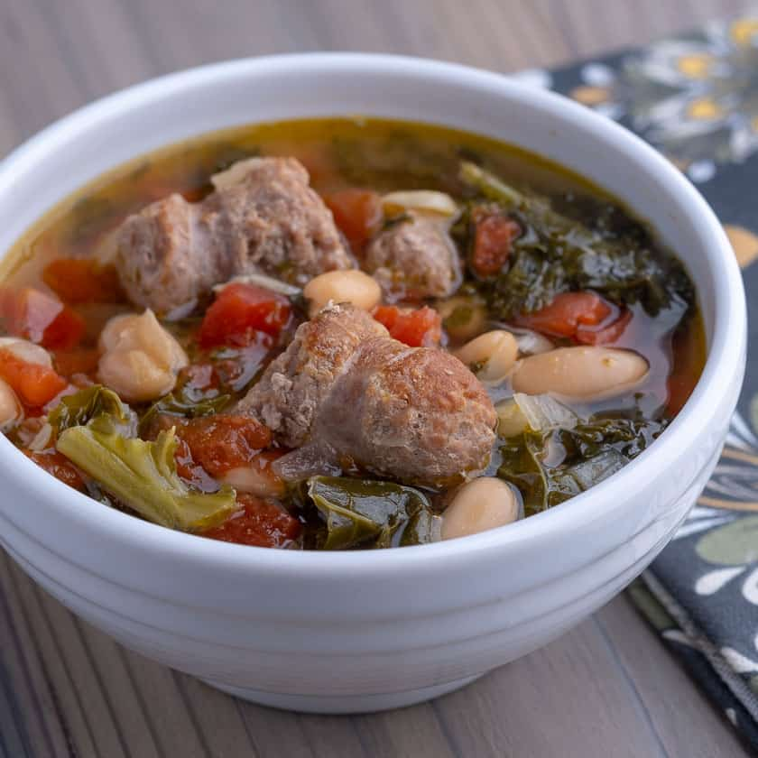 A white bowl of turkey sausage and kale soup, with beans and tomatoes, on a wooden table with a napkin.