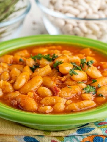 A bowl of cooked cannellini beans with tomatoes and pancetta, sprinkled with parsley, on a colorful napkin