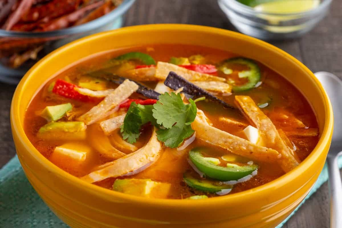 A yellow bowl of tortilla soup, with shreds of chicken, jalapeno peppers, tortilla strips, and cilantro, on a teal napkin, with lime wedges and chile peppers in the background.