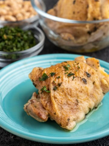 A chicken thigh, sprinkled with herbs, on a teal plate, in front of bowls of herbs and more chicken.