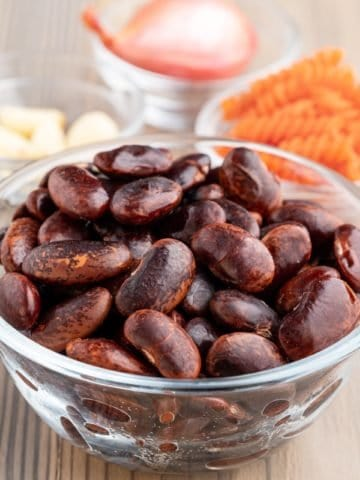 A bowl of cooked scarlet runner beans on a white table