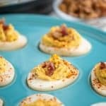 A turquoise plate of deviled eggs with bacon