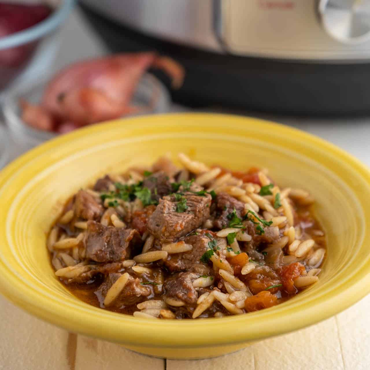 A yellow bowl of youvetsi - greek lamb stew with orzo