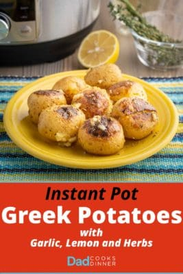 A plate of cooked potatoes, sprinkled with garlic and herbs, on a blue and yellow napkin with a pressure cooker, herbs, and a lemon in the background