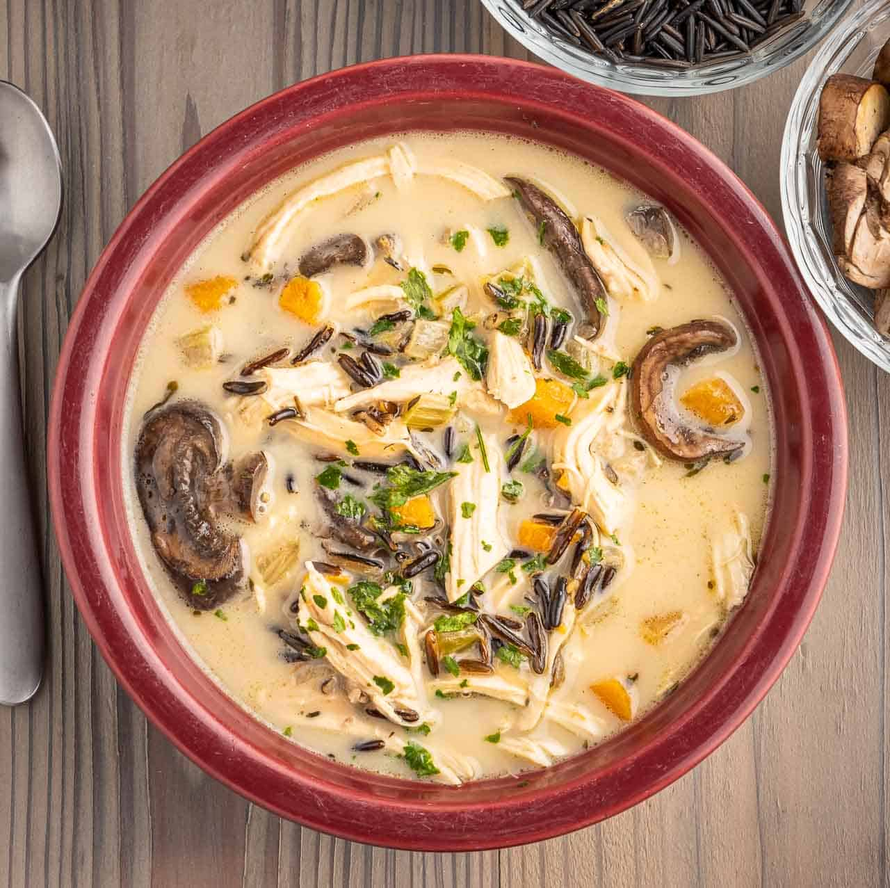 A creamy bowl of chicken and wild rice soup, with a spoon, some mushrooms, and some uncooked wild rice peeking in at the edges.