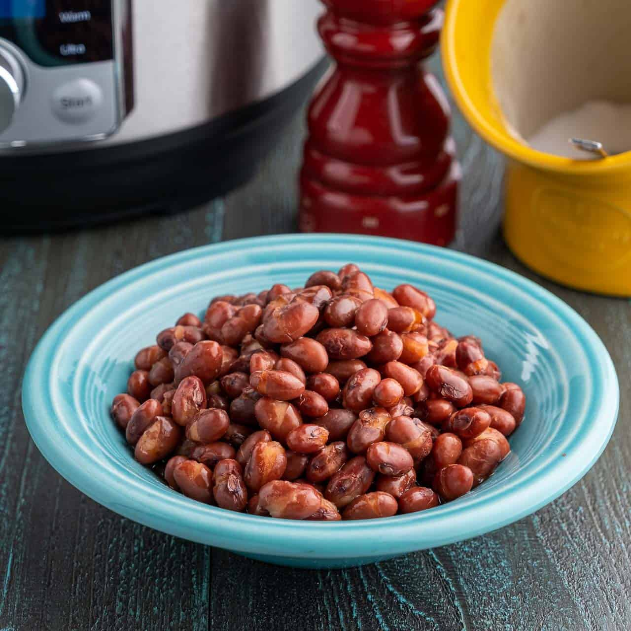 A bowl of red beans in front of a pressure cooker, a salt pig, and a pepper grinder