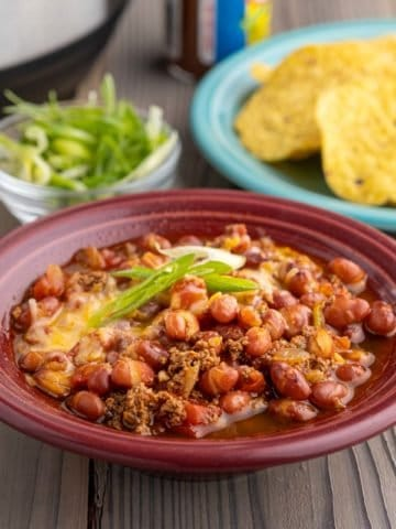 A bowl of turkey and small red bean chili, with minced green onions, tortilla chips, and an Instant Pot in the background.