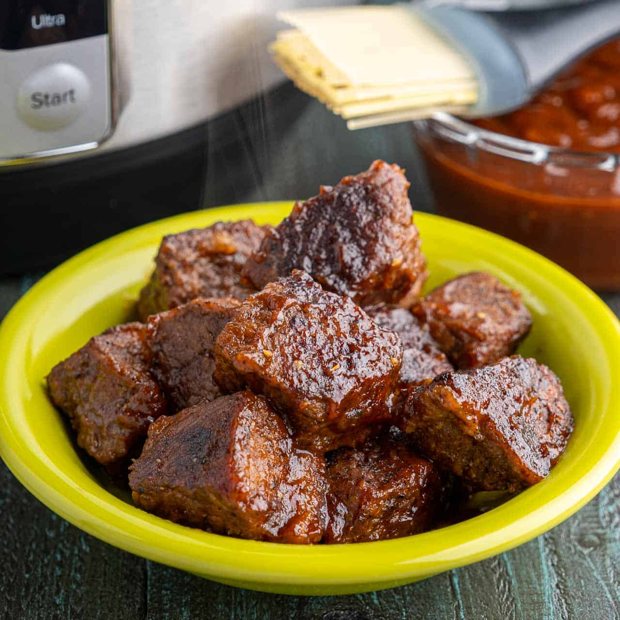 A bowl full of cooked brisket cubes, glazed with barbecue sauce, with an Instant Pot and a bowl of barbecue sauce in the background