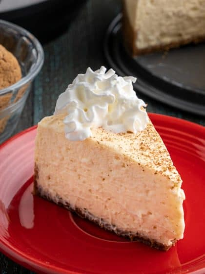 A slice of eggnog cheesecake on a red plate, with ginger snaps, an Instant Pot, and the rest of the cheesecake in the background