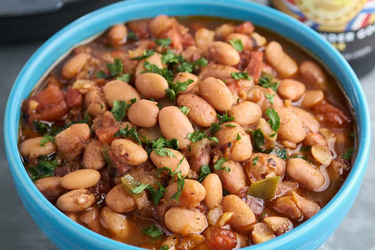 A blue bowl of borracho beans, pinto beans with bacon, tomato, and jalapeno, sprinkled with minced cilantro, with a bottle of beer and an Instant Pot in the background.