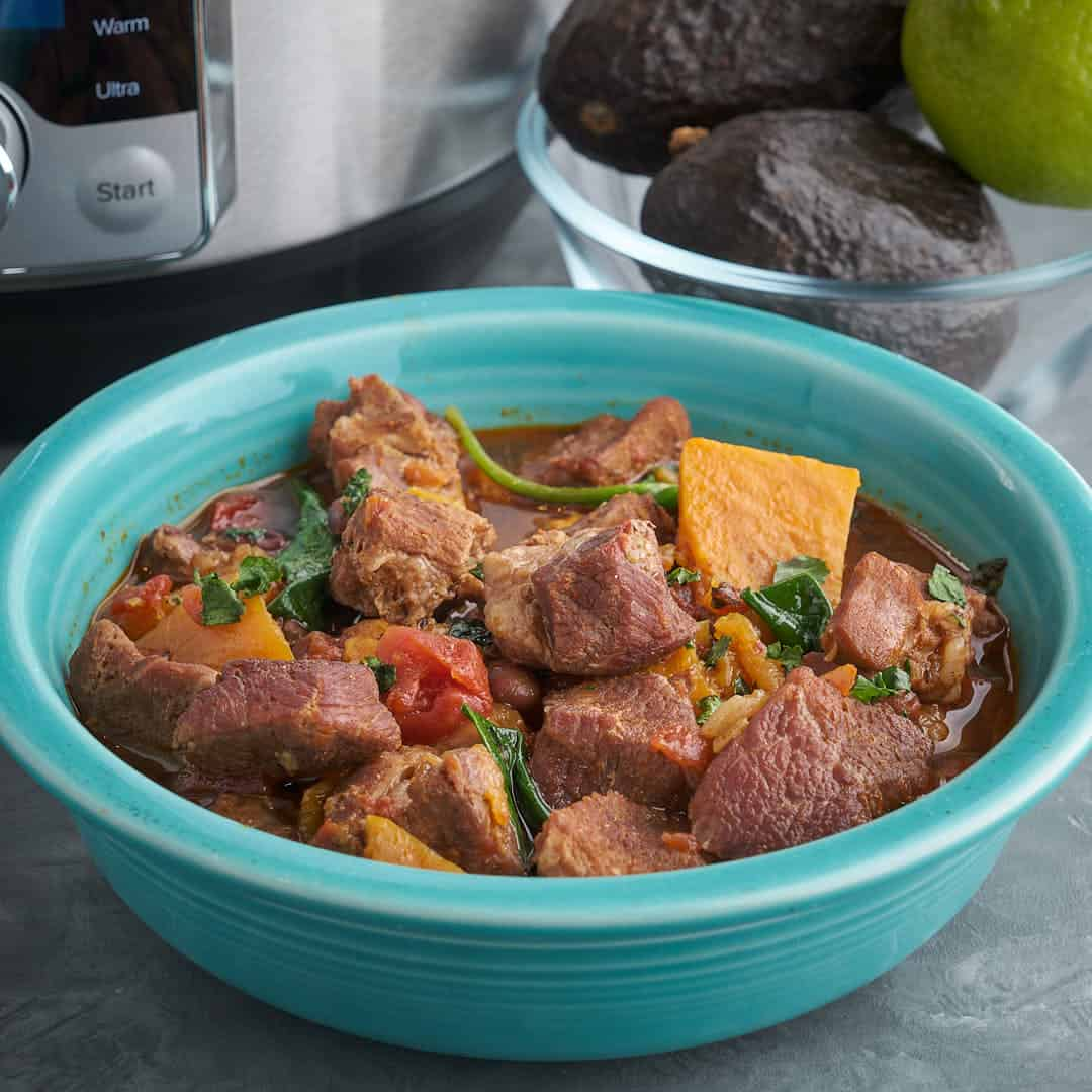A bowl of pork stew with sweet potatoes, tomatoes, and black beans, with a sprinkle of cilantro, and an Instant Pot and bowl of avocados in the background