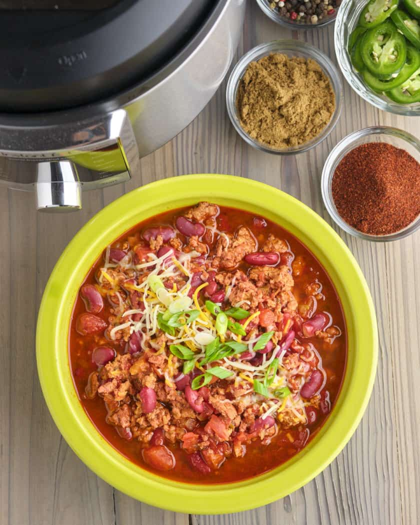 A bowl of ground pork and bean chili, sprinkled with cheese and chopped green onion, with spices, sliced jalapeños, and an Instant Pot in the background
