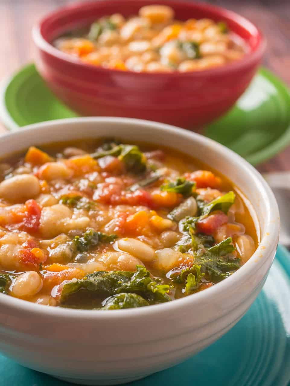 Two bowls of Tuscan bean soup on colorful plates