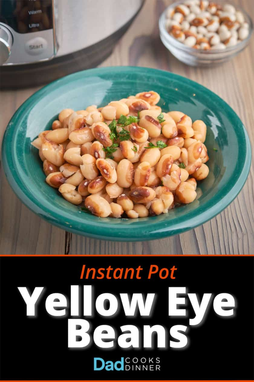 A bowl of cooked yellow eye beans on a wood table with an Instant Pot and some uncooked beans in the background
