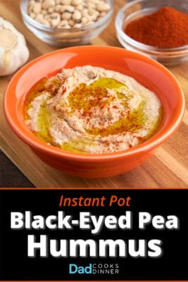 A bowl of black-eyed pea hummus, drizzled with olive oil and sprinkled with paprika, with a bowl of paprika, black-eyed peas, and garlic in the background