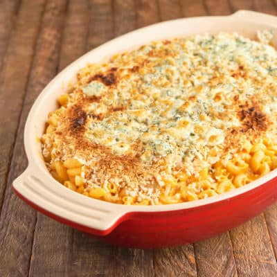A red baking dish full of Instant Pot Buffalo Chicken Mac and Cheese, topped with a browned crust of breadcrumbs and blue cheese