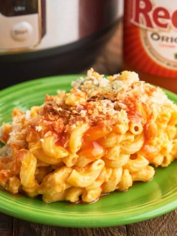 A plate of buffalo chicken mac and cheese in front of an Instant Pot and a bottle of Franks RedHot