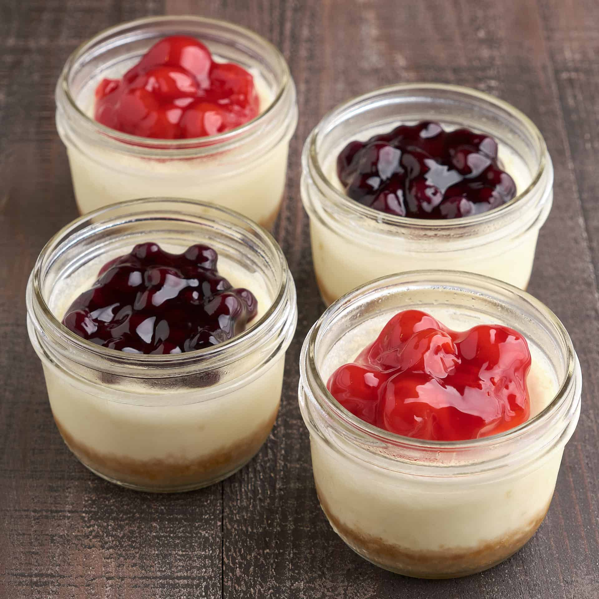 Four mini cheesecakes in canning jars, with cherry and blueberry topping, on a wood tabletop